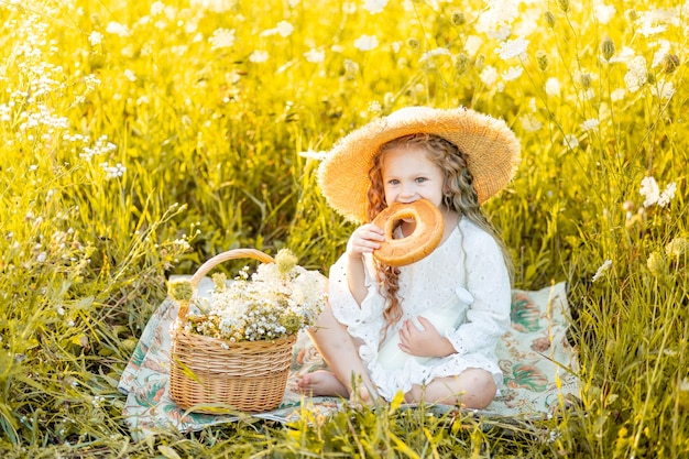 Beautiful little girl sitting in a straw hat in a yellow field with wild flowers with a bottle of milk and a bagel