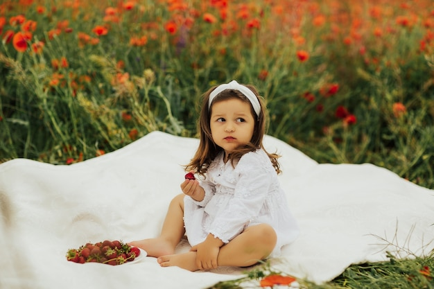 Beautiful little girl sitting on white plaid in a field of poppies and eating strawberries