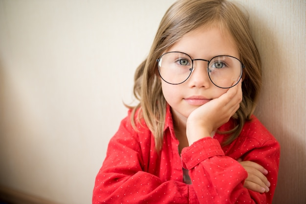 Beautiful little girl sitting with glasses and red clothes. copy space