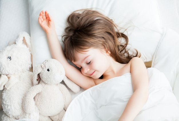 Beautiful little girl sleeping sweetly in a white bed with rabbit toys lying near. top view.
