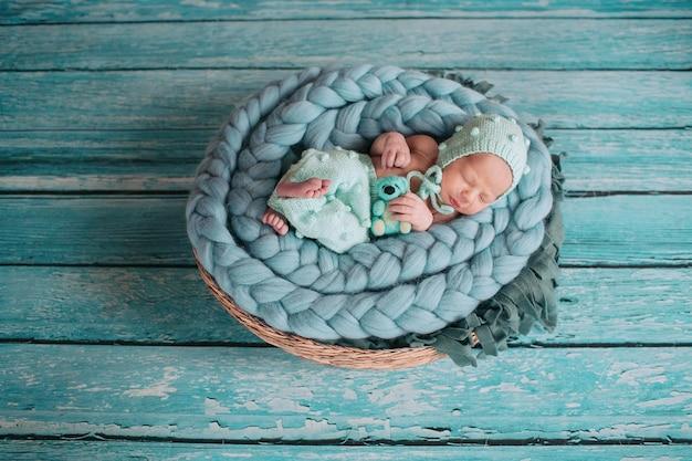 Beautiful little girl sleeps with blue bear on blue blanket in the basket