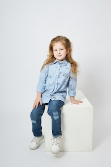 Beautiful little girl smiles, child in autumn clothes poses on a white background