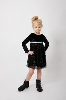 Красивая маленькая девочка улыбается, ребенок в осенней одежде позирует на белом фоне