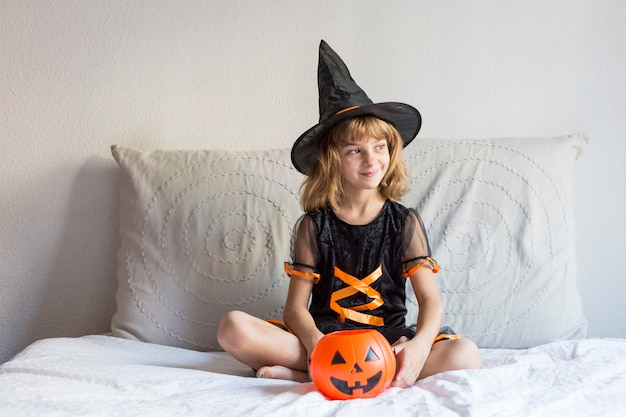 Beautiful little girl smiling on bed and wearing a halloween costume. playing with pumpkins