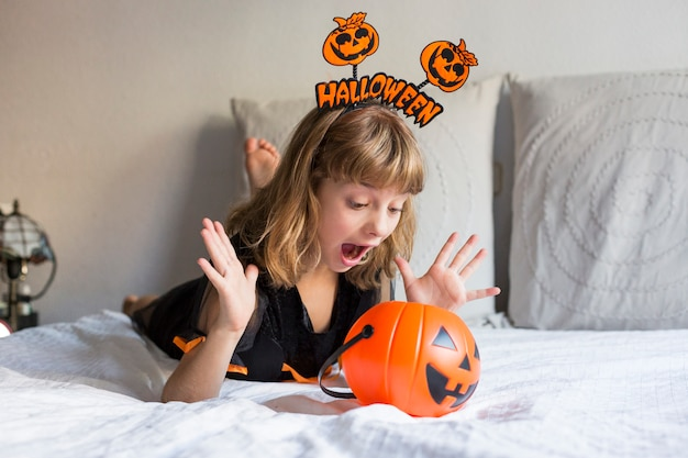 Beautiful little girl smiling and wearing halloween costume on bed. playing with pumpkins