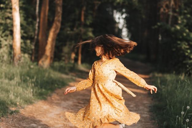 Красивая маленькая девочка крутится и танцует в лесу летом