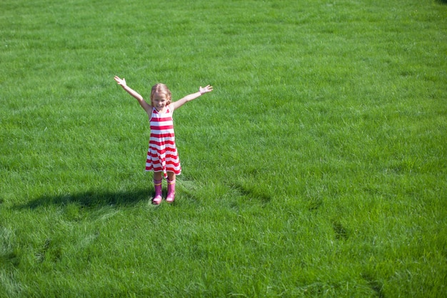 Beautiful little girl spread her arms standing on the lawn