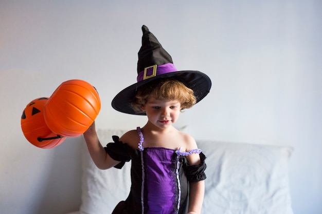 Beautiful little girl standing on bed and wearing a halloween costume. playing with pumpkins