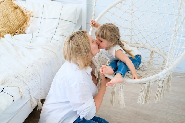 Beautiful little girl swinging in a hanging chair in the bedroom with her mom baby kisses mommy
