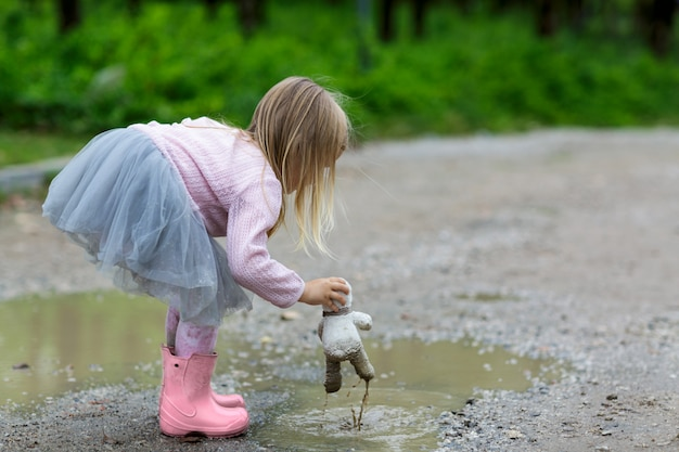 Beautiful little girl in a tutu skirt batting a teddy bear in a puddle on the street