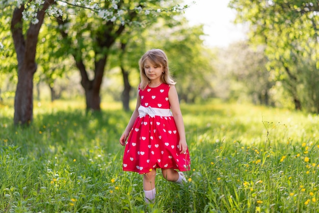 Beautiful little girl walks in the garden among the trees in spring