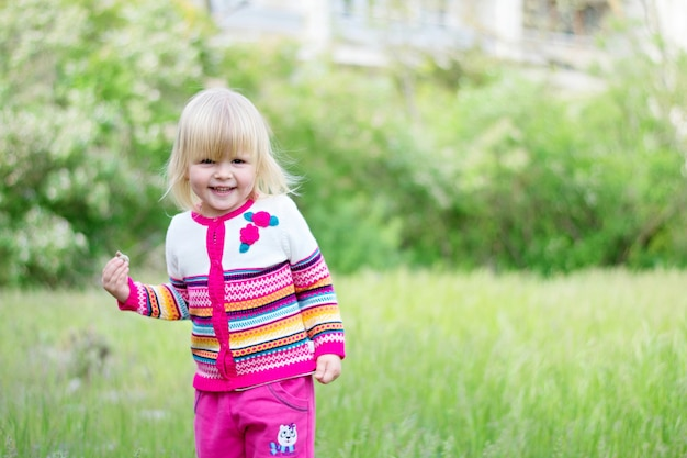 Beautiful little girl walks on the grass in spring