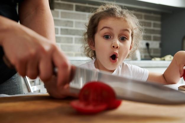 美しい少女は、母親がまな板でトマトを切るのを見ています。母と娘が一緒に食事を準備する