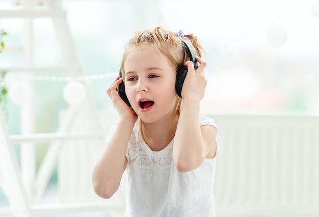 헤드폰을 착용하는 아름 다운 작은 소녀
