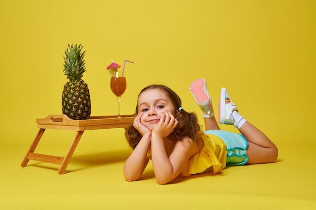 Красивая маленькая девочка в летней одежде, лежа на желтом фоне возле бамбукового подноса