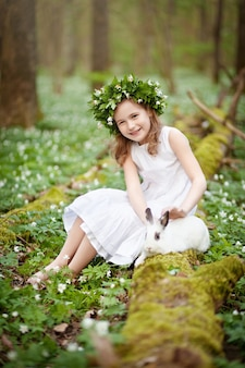 Beautiful little girl in a white dress plaing with white rabbit in the spring wood.