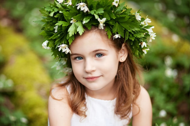 Beautiful little girl in a white dress in the spring wood. portrait of the pretty little girl with a wreath from spring flowers on the head.