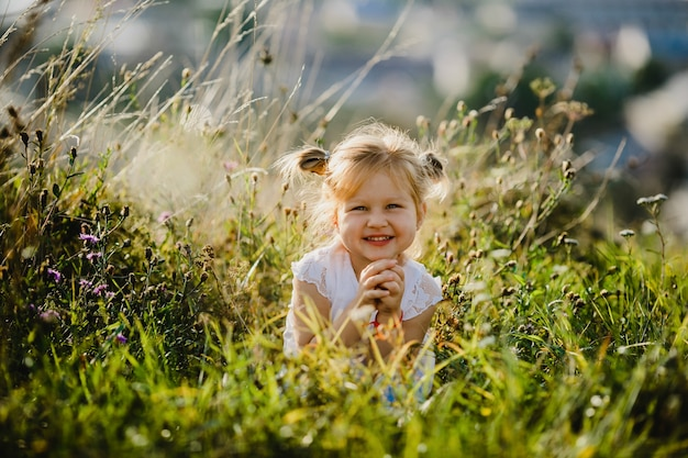 Beautiful little girl in white shirt and jeans sits  on the lawn with great landscape