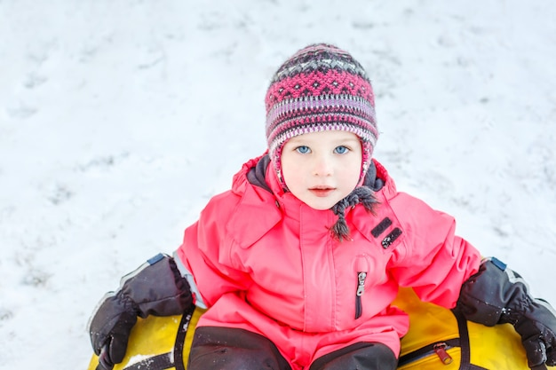 Beautiful little girl in winter clothes sitting on a snow tube in the snow.