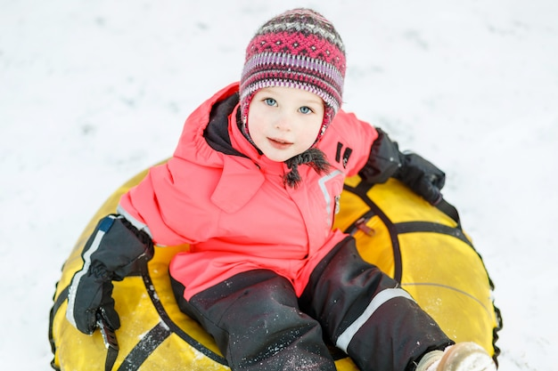 Beautiful little girl in winter clothes sitting on a snow tube