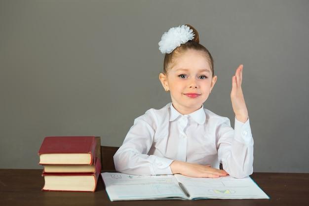 Красивая маленькая девочка с бантом на голове сидит за столом с книгами на серой стене