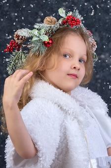 그녀의 머리에 크리스마스 화 환과 함께 아름 다운 작은 소녀. 크리스마스 아이.