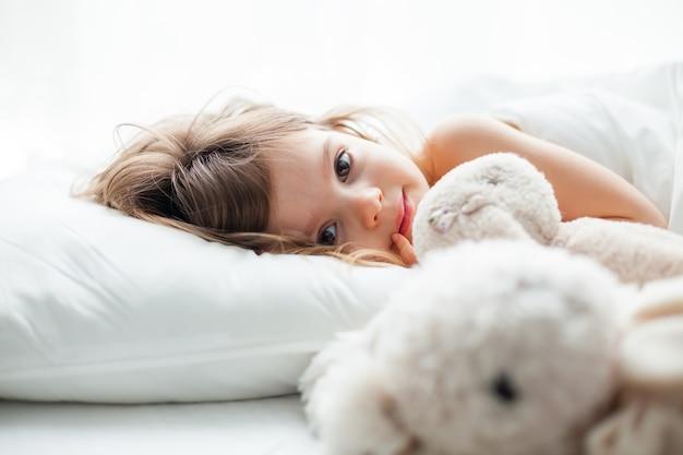 Красивая маленькая девочка с большими глазами, лежащая в белой кровати с игрушками-кроликами рядом с ней