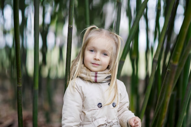 Beautiful little girl with blonde hair standing in a bamboo forest and shaking bamboo