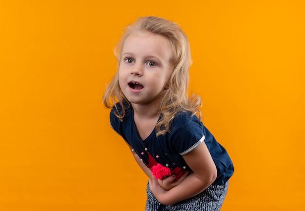 Una bella bambina con i capelli biondi che indossa una camicia blu navy che tiene il suo stomaco mentre si sente male su una parete arancione