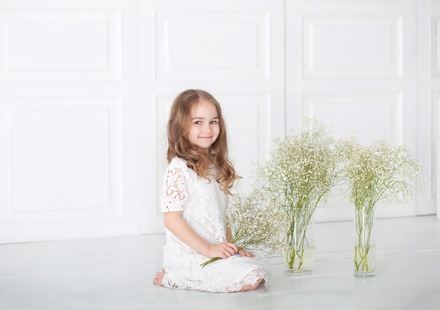 Beautiful little girl with a bouquet of gypsophila (baby-breathon). portrait girl with blond hair in a white dress holding a flowers. cute baby with a bouquet in hands.