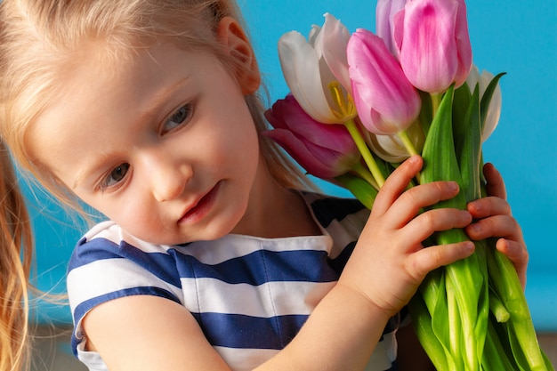 Beautiful little girl with bunch of tulips against blue background