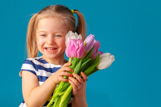 Beautiful little girl with bunch of tulips against blue wall