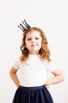 The beautiful little girl with crown and fashion dress isolated on white background. white t-short for design