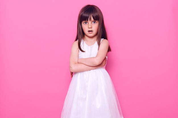 Beautiful little girl with dark hair keeping hands folded, looking at front with scared and astonished facial expression, keeps mouth opened, wears white dress, isolated over pink wall