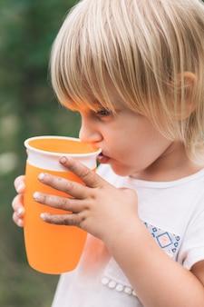 Красивая маленькая девочка с грязными руками, пить из чашки.