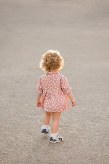 The beautiful little girl with a fair curly hair on walk in the park in warm summer day