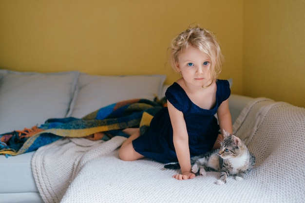 Beautiful little girl with fair hair sits on a sofa and plays with her cat.