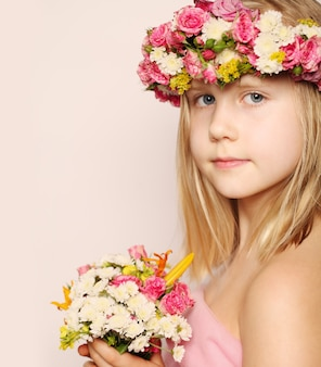 Beautiful little girl with flowers posing and looking