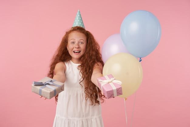 Bella bambina con capelli ricci foxy in abito bianco e berretto di compleanno felicemente guardando a porte chiuse, tenendo scatole regalo in mano, in posa su sfondo rosa e palloncini colorati