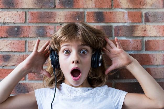 Красивая маленькая девочка с наушниками дома слушая к музыке и имея концепцию потехи, технологии и музыки