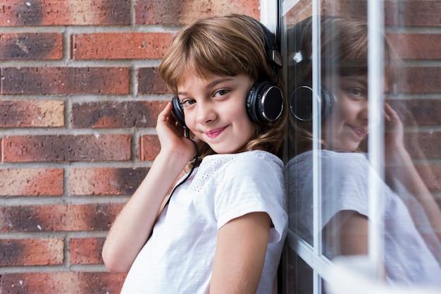 Красивая маленькая девочка с наушниками дома слушая к музыке и концепции усмехаться, технологии и музыки. стиль жизни