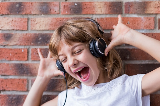 Beautiful little girl with headphones at home listening to music and singing, technology and music concept. lifestyle