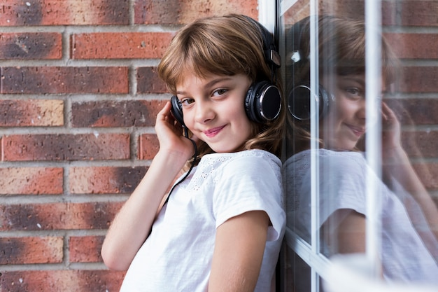 Beautiful little girl with headphones at home listening to music and smiling, technology and music concept. lifestyle