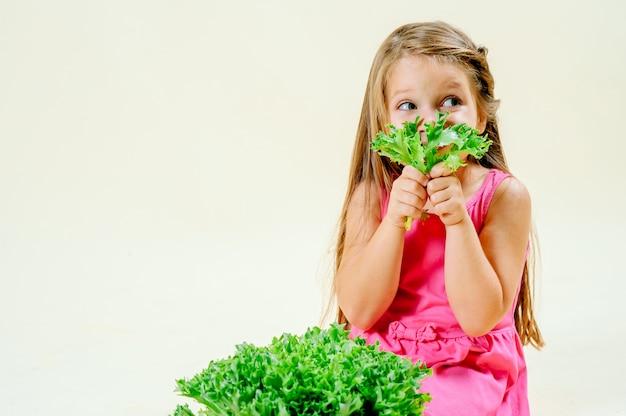 Beautiful little girl with lettuce in hand on a light monophonic background, proper nutrition