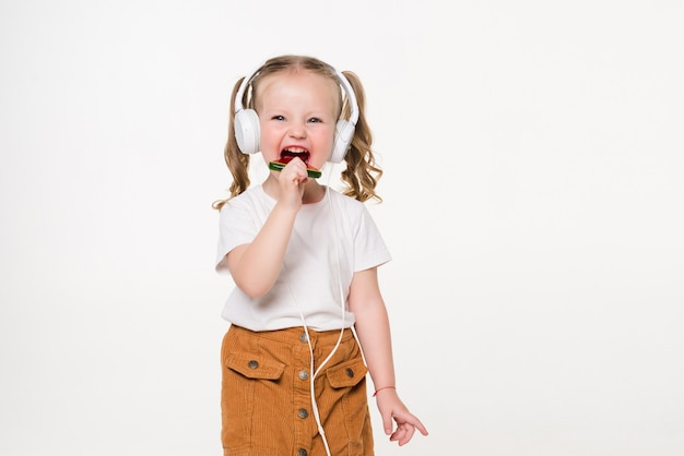 Beautiful little girl with lollipop listen music in headset isolated