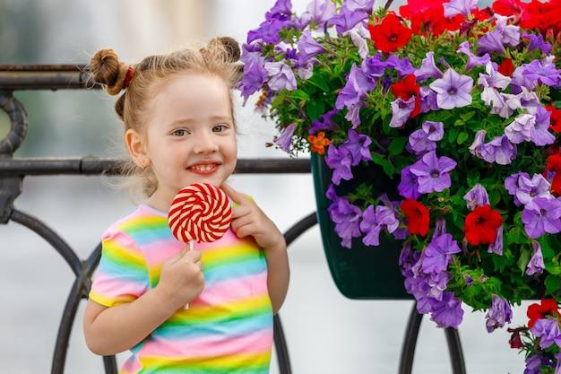 ロリポップを持つ美しい少女が花の近くに立っています