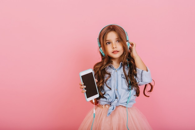 Beautiful little girl with long brunette hair with phone listening to music through blue headphones isolated on pink background. cheerful mood of young child, enjoying music