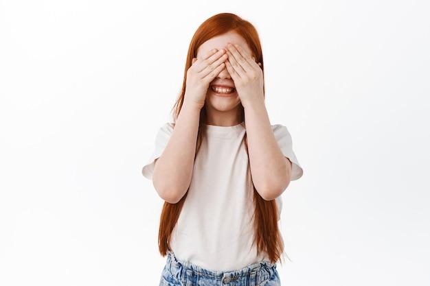 Красивая маленькая девочка с длинными рыжими волосами играет в прятки