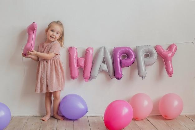 風船で白い背景に長い髪の美しい少女。子供の誕生日。