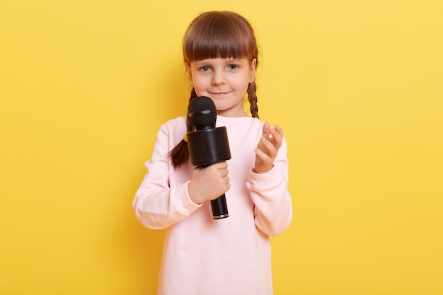 Beautiful little girl with microphone performing,  charming smile, raising hand, looks a bit shy, child model posing isolated over yellow wall.